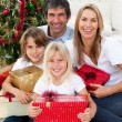 Smiling family holding Christmas presents — Stock Photo