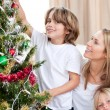 Stock Photo: Mother and her children decorating a Christmas tree
