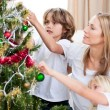 Children hanging Christmas decorations with their mother — Stock Photo