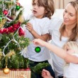 Smiling Mother and her children decorating a Christmas tree — Stock Photo