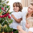 Happy mother and her children hanging Christmas decorations — Stock Photo