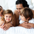 Parents and children lying on the bed — Stock Photo