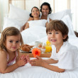 Smiling family having breakfast in the bedroom — Stock Photo
