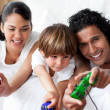 Portrait of smiling parents playing video games with their son — Stock Photo