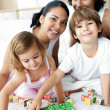Young family having fun with alphabetics blocks — Stock Photo