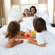 Happy family having breakfast lying on the bed — Stock Photo