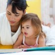Attentive mother reading with her little girl — Stock Photo #10293674