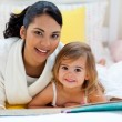 Portrait of a smiling mother and her daughter reading together — Stock Photo
