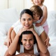 Young family having fun on the bed — Stock Photo #10293686