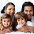 Happy family smiling at the camera - Stock Photo