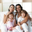Portrait of a smiling family sitting on the bed — Stock Photo #10293700