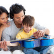 Happy little boy playing guitar with his parents — Stock Photo