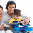 Cute little boy playing guitar with his parents — Stock Photo