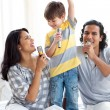 Adorable little boy singing with his parents — Stock Photo