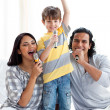 Lively young family singing with microphones — Stock Photo #10293767