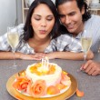 Pretty woman blowing up candles with her husband for her birthda — Stock Photo
