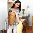 Blond little girl unpacking grocery bag with her mother - Foto Stock