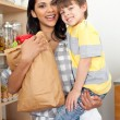 Adorable Little boy unpacking grocery bag with his mother — Stock Photo #10293830
