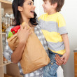 Stock Photo: Cute Little boy unpacking grocery bag with his mother