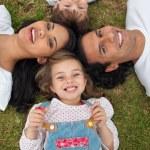 menina deitada em um círculo com sua família em um parque — Foto Stock