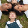 Foto Stock: Lively family lying in a circle on the grass