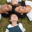 Cute children and their parents lying on the grass — Stock Photo #10293848