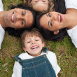 Foto Stock: Little boy lying in a circle with his family in a park