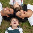 Joyful family lying in a circle on the grass — Stock Photo
