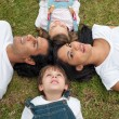 Stock Photo: Jolly parents and their children lying on the grass