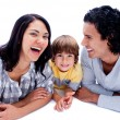 Laughing parents with their son lying on the floor — Stock Photo #10293868