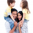 Smiling parents giving piggyback ride to their children — Stock Photo