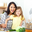 Stock Photo: Smiling mother and daughter cutting vegetables together