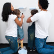 Foto Stock: Attentive parents helping their children paint
