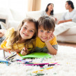 Adorable btother and sister drawing lying on the floor — Stock Photo