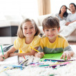 Royalty-Free Stock Photo: Portrait of cute siblings drawing lying on the floor