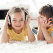 Children playing on the floor with headphones — Stock Photo