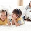 Little boy and little girl playing on the floor with headphones — Stock Photo