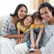 Joyful family sitting on sofa — Stock Photo #10293954