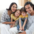 Joyful family sitting on sofa — Stock Photo