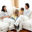 Attentive parents sitting on sofa with their children — Стоковая фотография