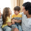 Cute siblings sitting on sofwith their parents — Stock Photo #10293959