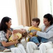 Stock Photo: Earing parents playing with their children on sofa