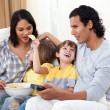 Merry family watching TV on sofa - Stock Photo