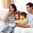 Lively family watching TV on sofa — Stock Photo