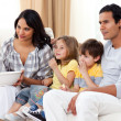 Smiling family watching TV on sofa — Stockfoto