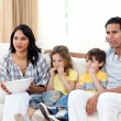 Concentrated family watching TV on sofa — Stock Photo