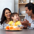 Joyful child celebrating his birthday with his parents — Stock Photo #10293985