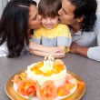 Cute child celebrating his birthday with his parents — Stock Photo #10293987