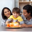 Smiling parents celebrating their son's birthday - Stock Photo