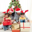 Happy family opening Christmas presents - Stock Photo